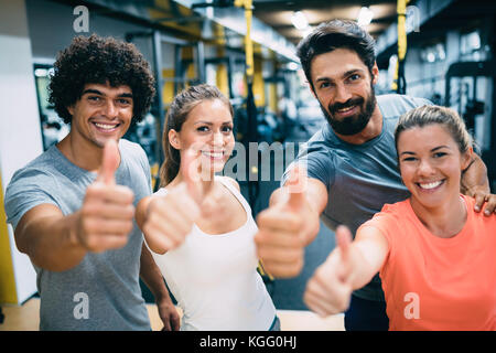 Portrait of cheerful fitness team in gym - Stock Photo