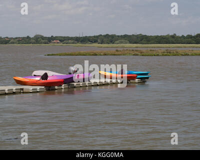 Brightly coloured kayaks on the river Alde at Iken - Stock Photo