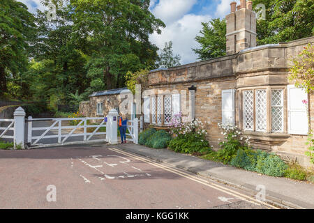 A woman makes her way past the old Toll Cottage and Gate on Quarryheads lane, towards South Bailey and Prebends - Stock Photo