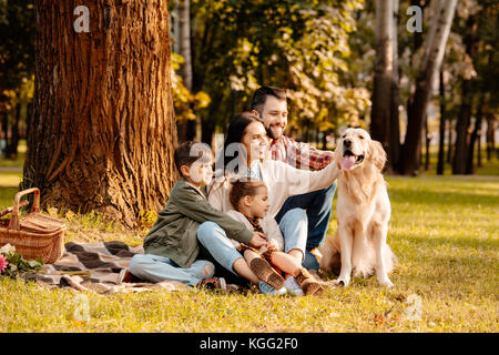 Family on picnic petting dog - Stock Photo