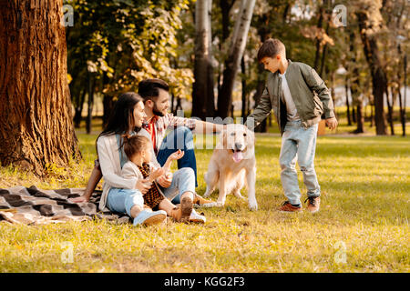 Family playing with dog in park - Stock Photo