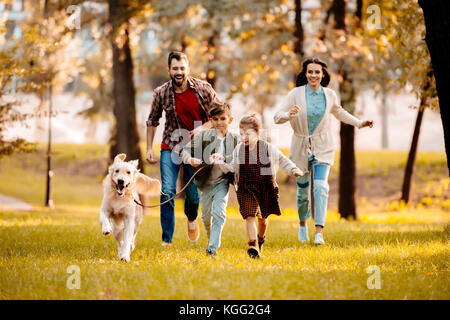 family running with dog in park - Stock Photo