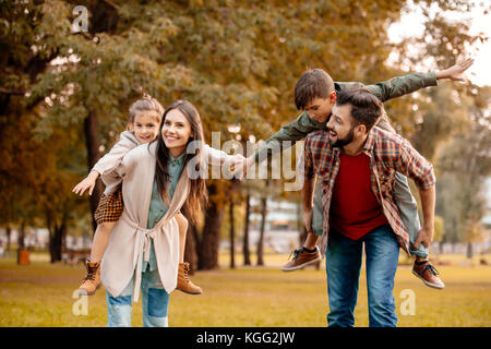 Parents giving children piggyback ride - Stock Photo