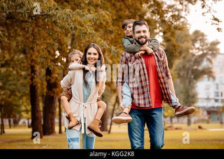 Parents giving children piggyback ride - Stock Photo