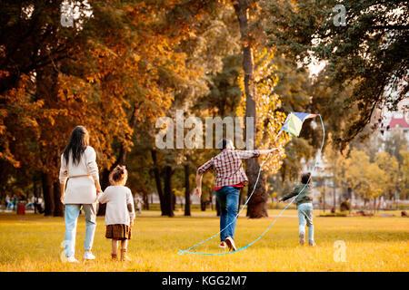 Family flying kite in park - Stock Photo