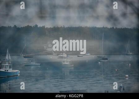 View on harbor with fishing and sailing boats through lobster net - Stock Photo