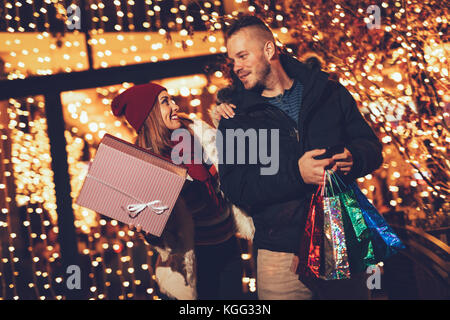 Young couple standing outside with shopping bags and boxes and enjoying an evening stroll through town at Christmas - Stock Photo