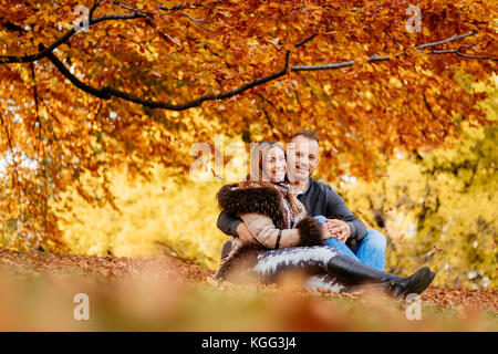 Beautiful smiling couple enjoying in sunny forest in autumn colors. They are sitting on the falls leaves and looking - Stock Photo
