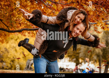 Beautiful young couple enjoying a piggyback in sunny park in autumn colors. Looking at camera. - Stock Photo