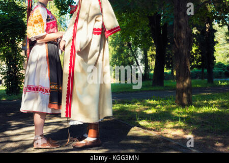 Young anonymous couple in folklore costumes - Stock Photo