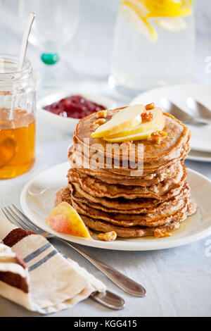 Stack of homemade whole wheat pancakes with fruits and nuts - Stock Photo