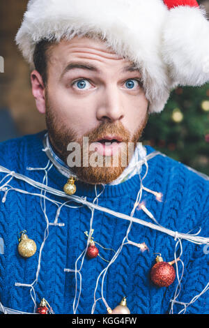 man tied up with christmas garland - Stock Photo