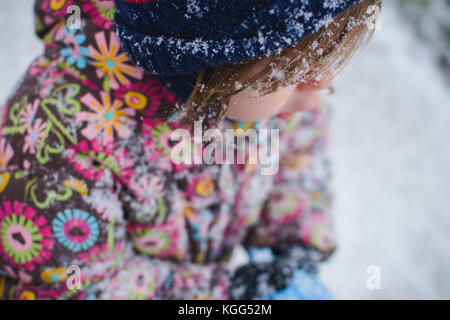 A toddler stands outside wearing winter clothes with snow around her. - Stock Photo