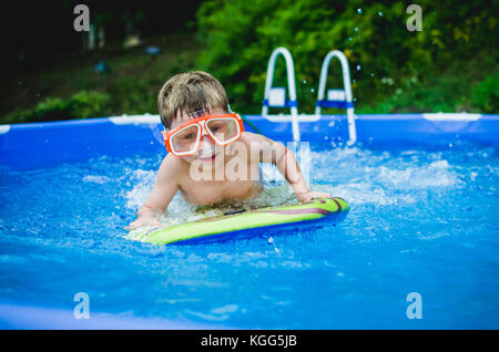 8-9 year old playing on a boogie board in a pool in summer. - Stock Photo