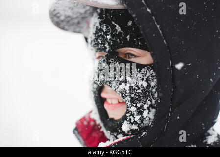 Child wearing a ski mask covered in snow - Stock Photo