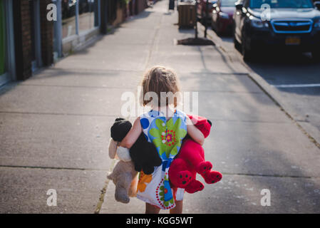 a little girl walks down a sidewalk with a handful of stuffed animals - Stock Photo