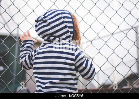 Child hangs on a fence and looks through it. - Stock Photo