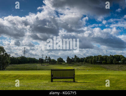 Wooden bench overlooking the sixteenth fairway at Manchester Golf Club, England UK - Stock Photo