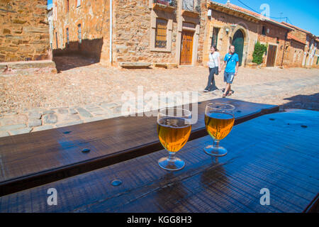 Two glasses of beer in a terrace and young couple walking along the street. Castrillo de los Polvazares, Leon province, - Stock Photo