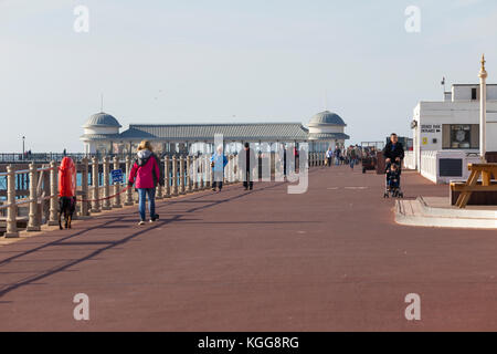 People walking along Hastings promenade with the pier in the background - Stock Photo