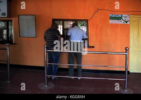 Peradeniya Junction Station Kandy Central Province Sri Lanka Men buying tickets station has free wifi - Stock Photo