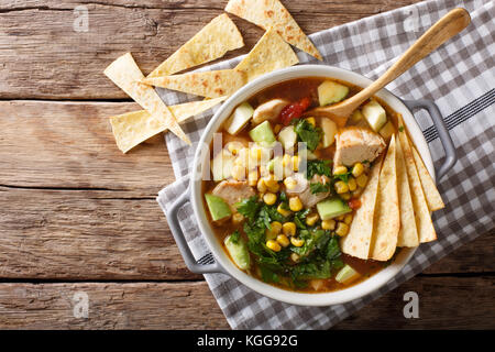 Freshly cooked tortilla soup with chicken and vegetables close-up on the table. Horizontal top view from above - Stock Photo