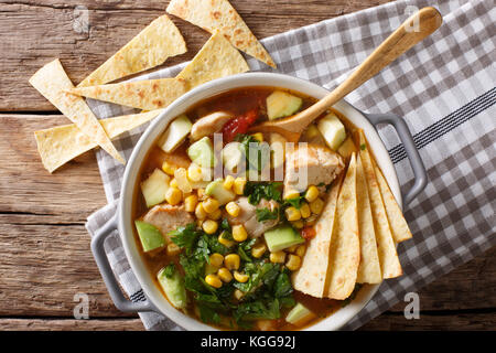 Mexican food: tortilla soup with chicken, tomatoes, avocado and corn close-up in a saucepan on a table. horizontal - Stock Photo