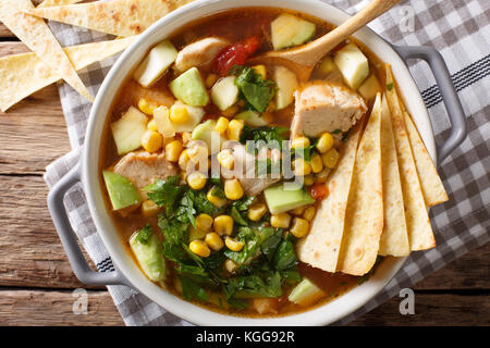 spicy tortilla soup with chicken, cilantro, tomatoes, avocado and corn close-up on the table. horizontal top view - Stock Photo