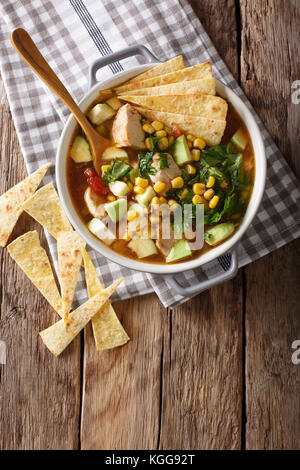 Freshly cooked tortilla soup with chicken and vegetables close-up on the table. Vertical top view from above - Stock Photo