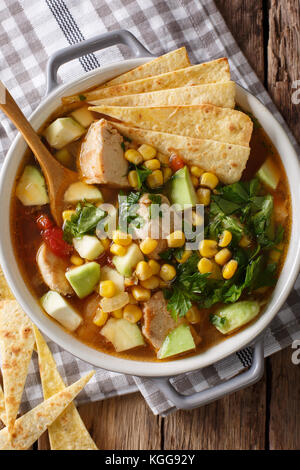 spicy tortilla soup with chicken, cilantro, tomatoes, avocado and corn close-up on the table. Vertical top view - Stock Photo