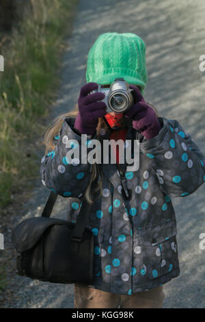 A young girl dressed in winter clothes plays with an old digital camera - Stock Photo