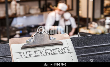 Week menu clipboard with restaurant kitchen and two cooks busy in the background. - Stock Photo