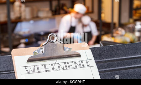 Week menu clipboard with restaurant and two cooks busy blurred in the background. - Stock Photo