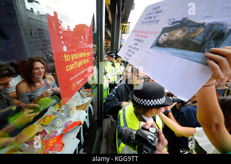 Vegan activists besieging a McDonalds restaurant in Whitehall London during an animal rights protest demonstration - Stock Photo