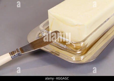 Knife and pack of butter in a butter dish - Stock Photo