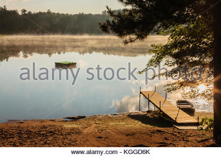 The mid-July early morning cooler air creates a light fog over Patricia Lake in northern Wisconsin, as the reflecting - Stock Photo