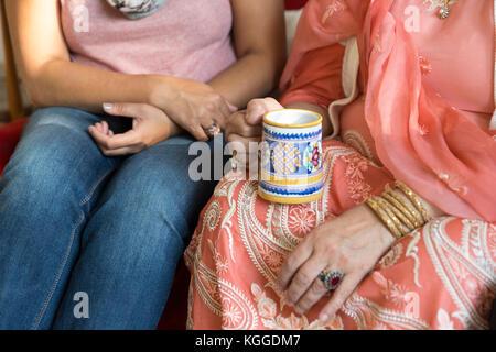 Indian woman in sari holding mug - Stock Photo