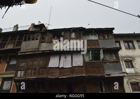 An old Nepali lady staring out the window into the streets in a wooden house with a compilation of windows and shutters - Stock Photo