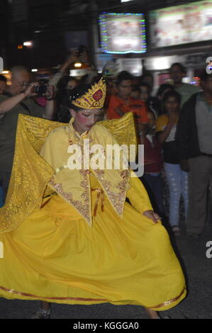 Girl in yellow dress dancing on the street at Nepalese news year's eve in April, Phokara, Nepal. - Stock Photo