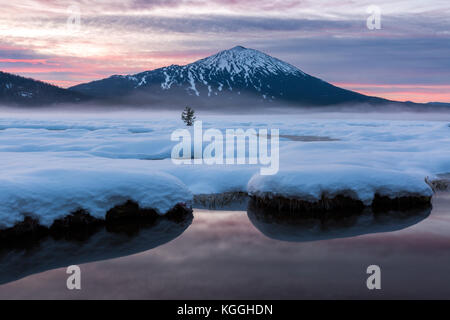 Mount Bachelor sits above a snowy field and lake during a colorful sunrise in Bend, Oregon. - Stock Photo