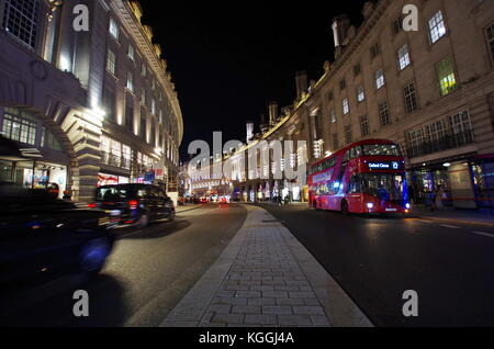 LONDON,UK - CIRCA OCT 2017 - Tourists and the typical red bus on Regent's street, near Piccadilly Circus. - Stock Photo
