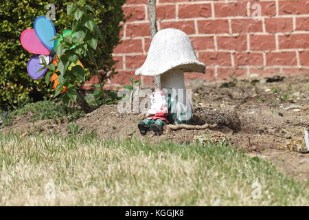 Statue of a gnome outside in the garden - Stock Photo