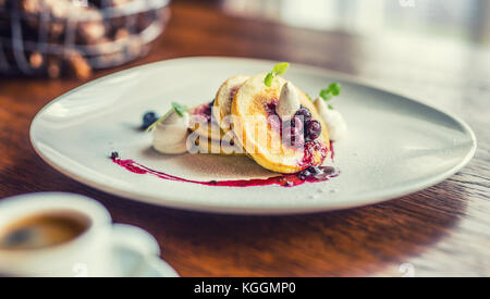 Pancakes and coffee. Pancakes with a cup of coffee and fresh fruits blueberries and herb decoration. Traditional - Stock Photo