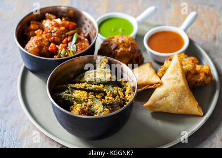 Selection of Indian dishes: samosas, onion bhaji, manchurian balls and okra - Stock Photo