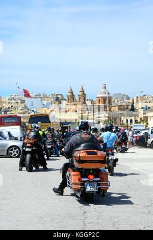 Group of motor cyclists parking with the parish church of Our Lady of Pompei to the rear, Marsaxlokk, Malta, Europe. - Stock Photo