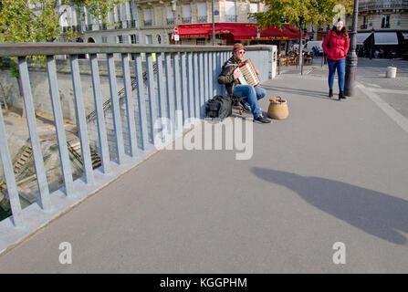 Paris, France. Pont Saint-Louis, accordion player busking - Stock Photo