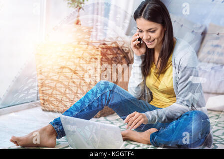 Pleasant conversation. Cheerful nice young woman sitting comfortably on the floor and looking at the screen of her - Stock Photo