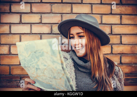 Happy smiling woman tourist  with exploring map while standing in alley near vintage building, trendy woman traveler - Stock Photo