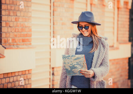 Happy woman tourist  with exploring map while standing in alley near vintage building, trendy woman traveler with - Stock Photo