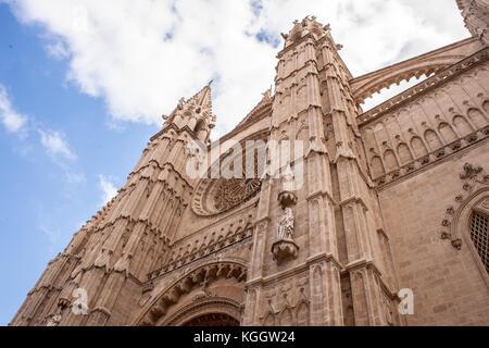 Cathedral Le Seu in Palma de Mallorca, a popular tourist destination, against a blue sky with clouds - Stock Photo